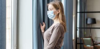 Kobieta wygląda z mieszkania przez okno w maseczce chirurgicznej